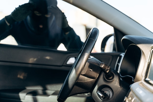 View from the car at the man dressed in black with a balaclava on his head looking at the glass of car before the stealing. car thief, car theft concept