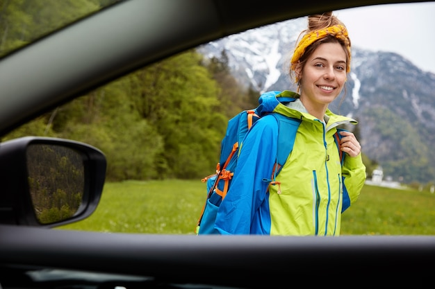 View from car window of happy female climber stands outdoor against beautiful mountain view