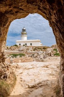 Вид из туннеля каваллерии на маяк (faro de cavalleria). менорка, балеарские острова, испания (вертикальное фото)