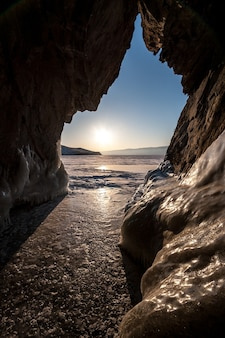View from the cave to winter lake baikal with ice in sunny weather