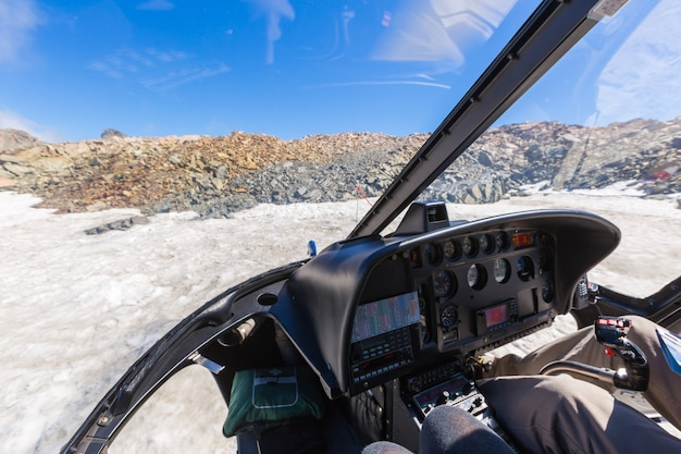 View from of cockpit of a helicopter as it flies over the fox glacier