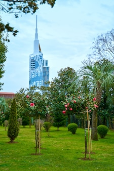 View from a colorful green park to a modern glass building with a spire