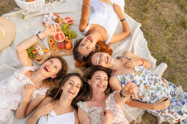 View from above. company of beautiful girlfriends have fun and enjoy a picnic outdoors.