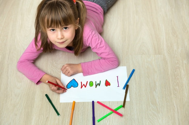 View from above of cute child girl drawing with colorful crayons i love mom