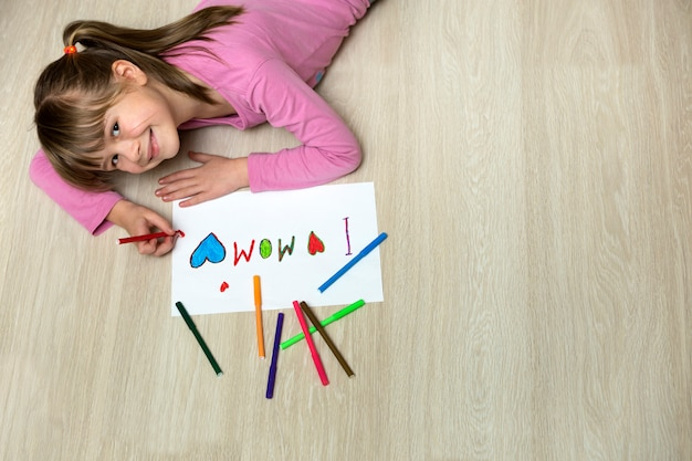 View from above of cute child girl drawing with colorful crayons
