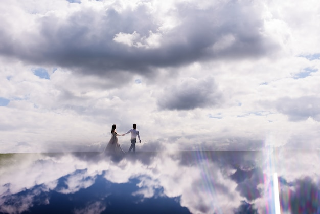 View from distance newlyweds walk in the clouds