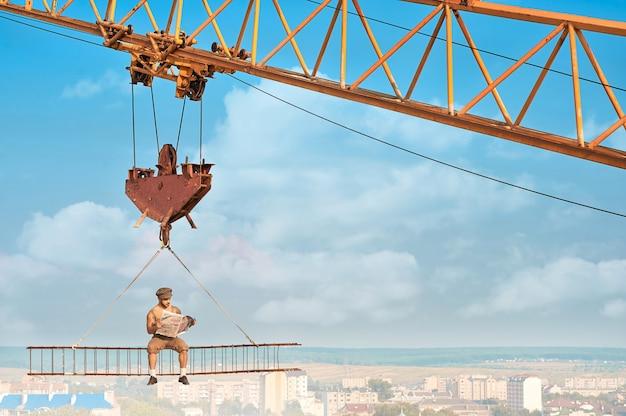 Вид с расстояния смелого строителя в рабочей одежде, сидящего на стройке на высоте и читающего газету. строительный кран, держащий строительство с человеком над городом. экстремальная застройка дома в большом городе.
