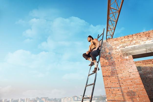 Вид с расстояния строителя с голым торсом и шляпой, сидящего на лестнице. опираясь на кирпичную стену на высоком. человек смотрит в сторону. голубое небо в летний сезон на фоне.
