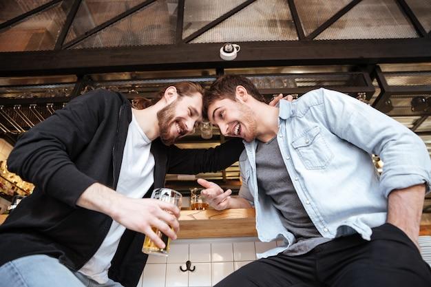 Vista dal basso di amici ubriachi sulla barra