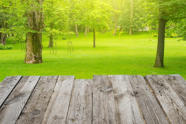 View from empty wooden deck table to the green spring foliage bokeh background