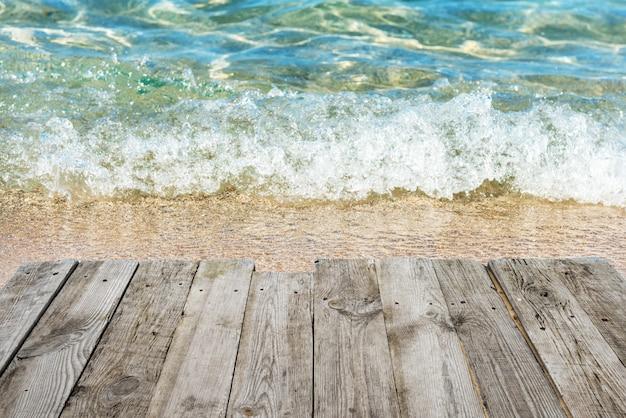 빈 나무 데크 테이블에서 서핑과 푸른 물이있는 열대 햇살 가득한 해변까지보기