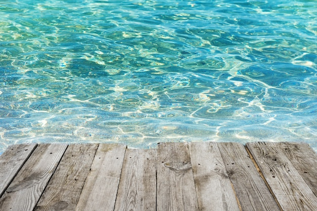 View from empty wooden deck table to tropical sunny beach with blue water background