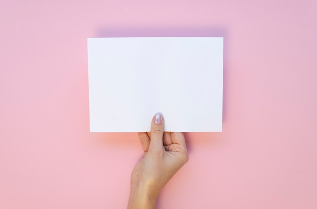 View from above female hand holds blank paper sheet mockup on a pastel pink background.