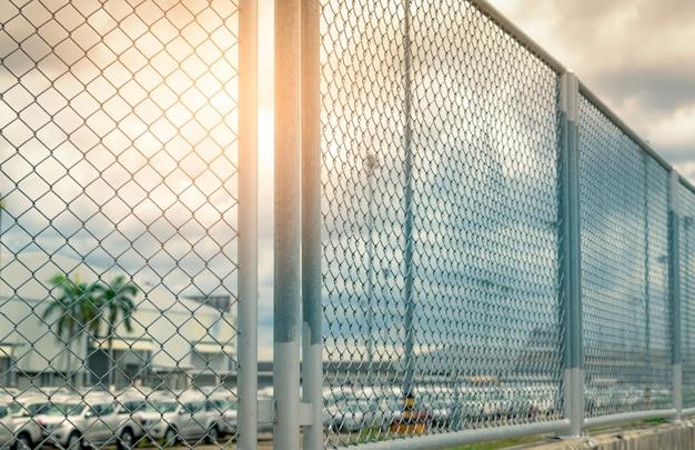 自動車製造工場のフェンスから新車在庫のぼやけた駐車場を見る。