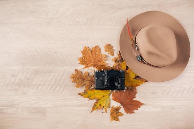 Vista dall'alto sulla disposizione piatta di stile donna e accessori, tendenza moda foglie d'autunno, macchina fotografica vintage, vestito da viaggiatore