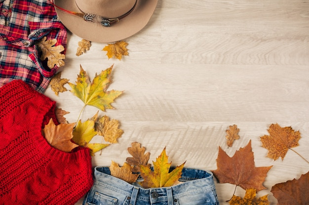 View from above on flat lay of woman style and accessories, red knitted sweater, checkered flannel shirt, denim jeans, hat, autumn fashion trend, traveler outfit