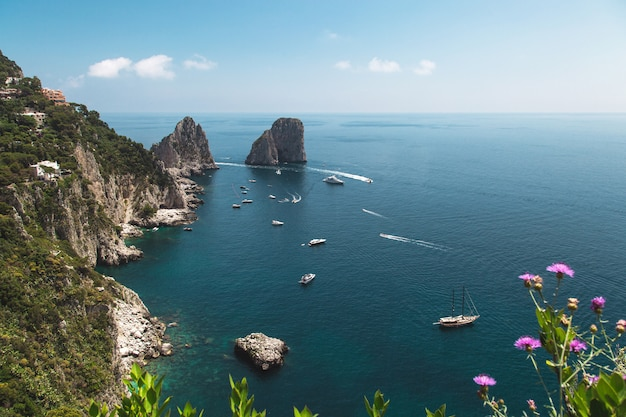 View from the gardens of augustus on capri coast and faraglioni rocks.