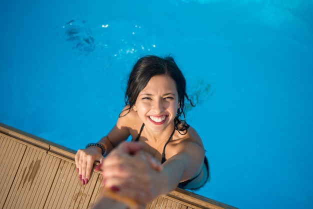 View from above of girl with snow-white smile in the swimming pool holding a man's hand trying to get out at sunny day