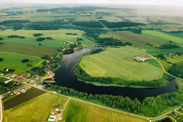 View from the height of the lake in a green field in the form of a horseshoe and a village in the mogilev region