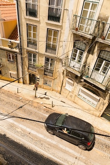 View from a high building of street with car and dwelling house