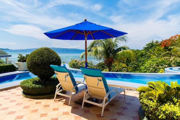熱帯のビーチと海のインフィニティプールの前にサンラウンジャーとパラソルがあるホテルからの眺め