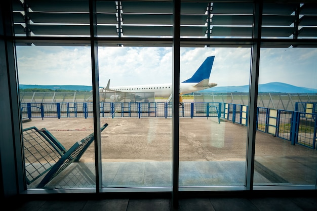 View from inside of airport terminal on the plane on runway