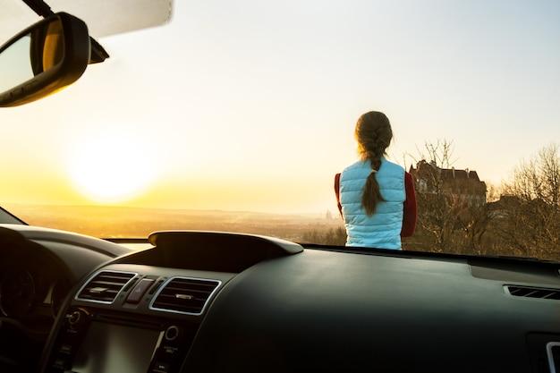 暖かい夕日の景色を楽しんでいる彼女の車の近くに立っている若い女性の中からの眺め。夜の地平線を見ている車のボンネットに寄りかかって女の子の旅行者。