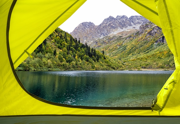 산 호수와 나무에 노란색 캠핑 텐트 내부에서 볼 수 있습니다. 여행 배경 프리미엄 사진