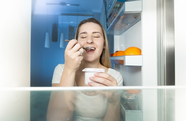 View from inside of refrigerator on young woman eating yogurt at night