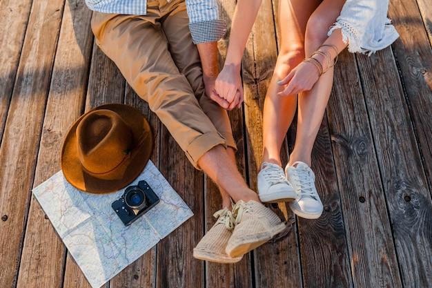Vista da sopra le gambe delle coppie che viaggiano in estate vestite di scarpe da ginnastica