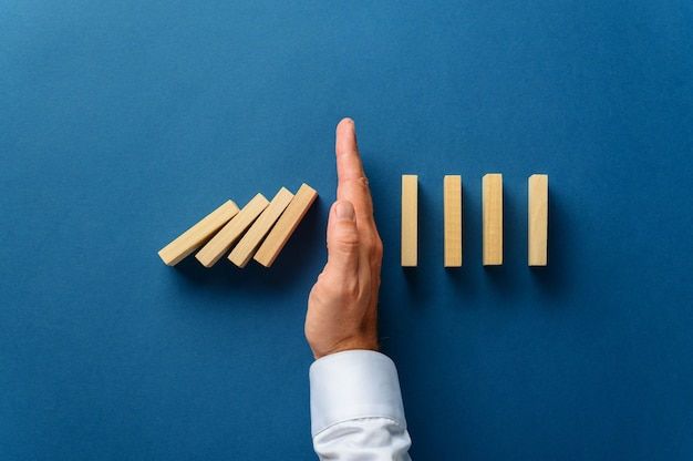 View from above of male hand interfering collapsing dominos in a conceptual image of business crisis management.