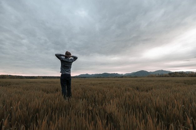 View from behind of a man standing in golden autumn meadow