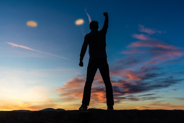View from behind of a man standing on top of a wall with his arm raised high in triumph under a beautiful glowing evening sky.