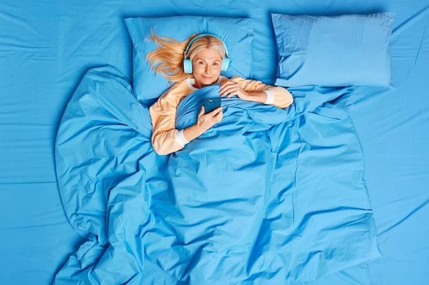 Vista dall'alto della donna di mezza età utilizza smartphone e cuffie stereo per ascoltare musica rilassante pone in un comodo letto gode di un nuovo giorno ha dormito abbastanza si trova sul morbido cuscino sotto la coperta blu