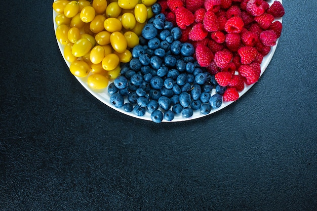 View from above. a mix of yellow, red and blue berries in a white grater. triangle separation. summer mix of fruits. berry layout