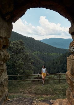 View from a natural window of a female traveler smiling and looking at the mountains