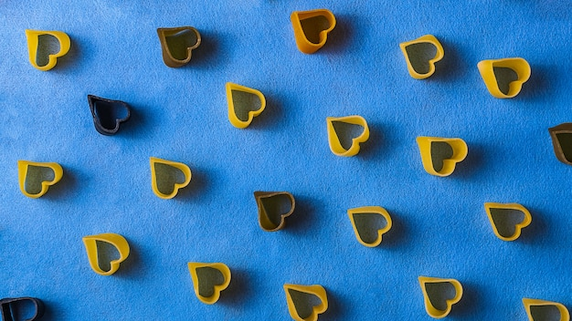View from above on pasta pattern with heart shape on blue paper background.