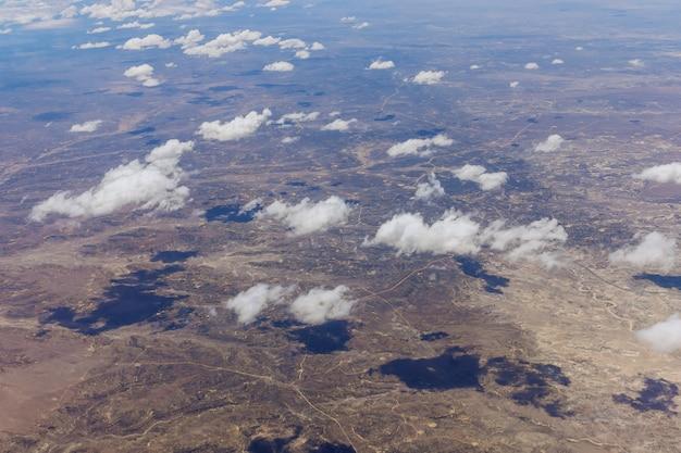 미국 뉴멕시코 사막의 푹신한 구름 위로 비행하는 동안 비행기에서 보기