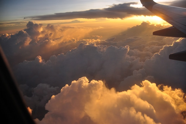 View from plane in flight of majestic clouds in golden sunset light illuminating air.