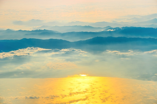 View from a plane to sunset on the sky with sunrays. fluffy clouds background