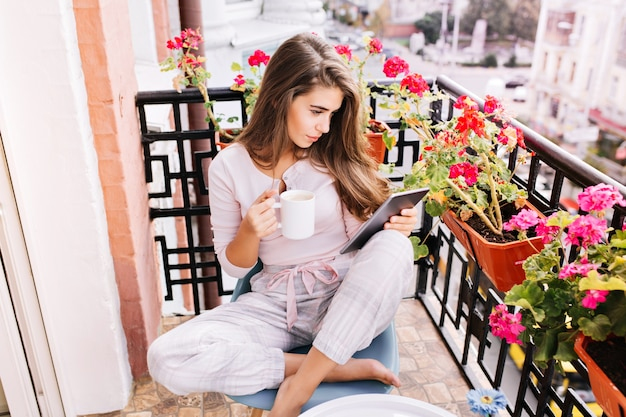 Vista dall'alto bella ragazza in pigiama facendo colazione sul balcone la mattina in città. tiene una tazza, leggendo sul tablet.