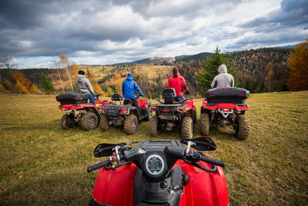 View from quad bike. four men at atv enjoying beautiful landscape
