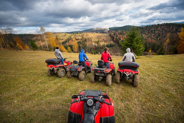 View from quad bike with four men at atv in front on the top of hill