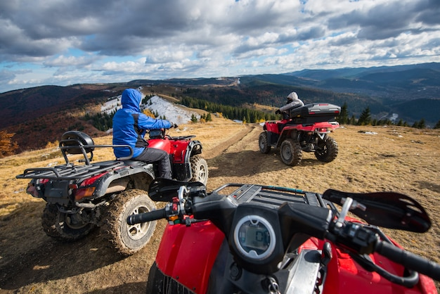 View from a quad bike with men driving an atv in front on the top of mountain trail