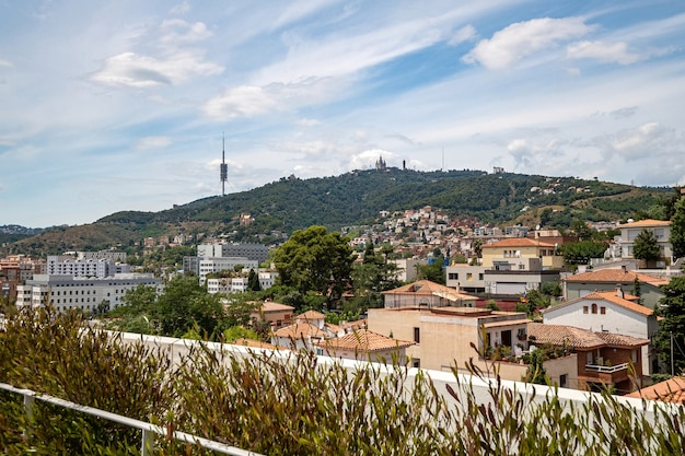 View from a rooftop of typical living area in barcelona with antenna and mountain