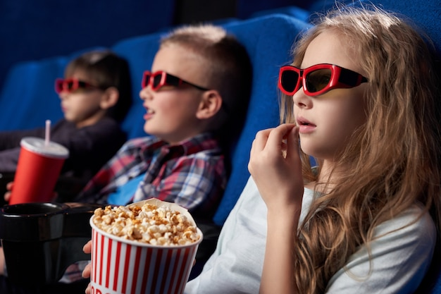 View from side of girl wearing 3d glasses eating popcorn