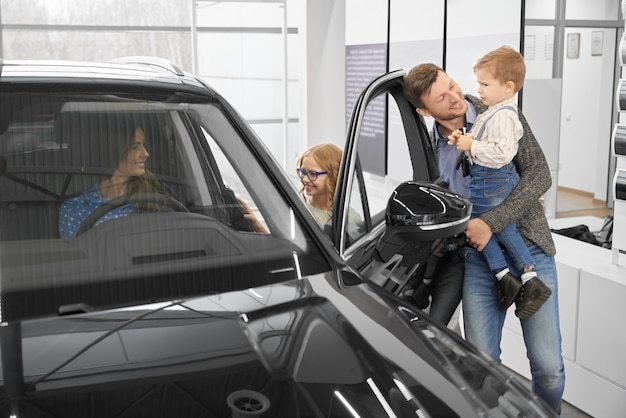 View from side of happy family looking at new black car in auto salon.