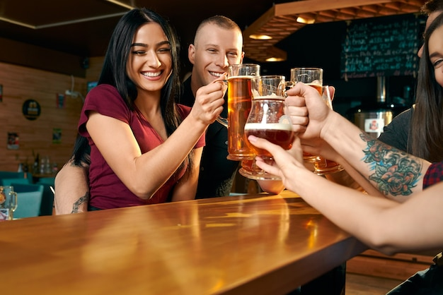 View from side of happy woman and man hugging each other and toasting with friends in pub. company drinking beer, laughing and enjoying free time together. concept of happiness and beverage.