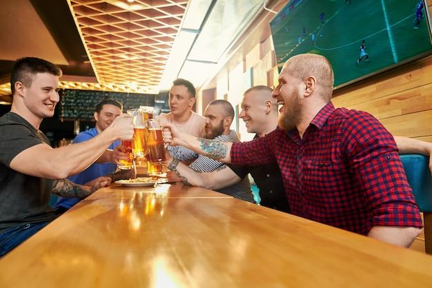 주말에 술집에서 함께 쉬고 쾌활한 남성 회사의 측면에서 볼 수 있습니다. 맥주를 마시고, 토스트하고, 웃고, 바에서 말하는 행복한 남자. 행복과 재미의 개념.