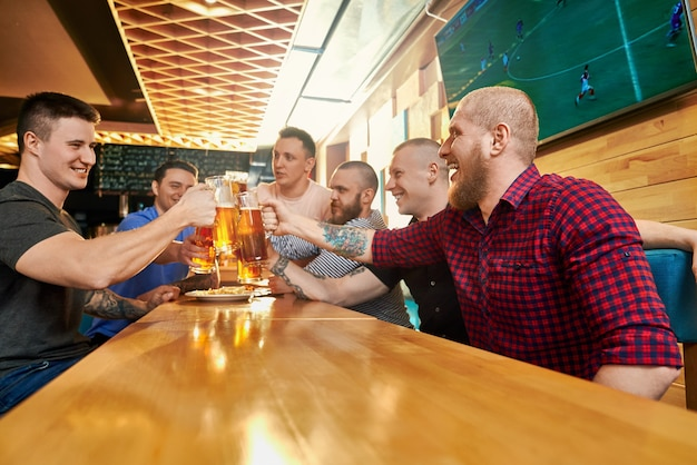 주말에 술집에서 함께 쉬고있는 쾌활한 남성 회사의 측면에서보기